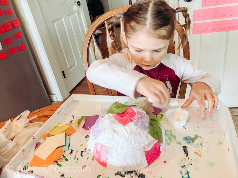 A little girl decorating a plastic bowl with tissue paper.
