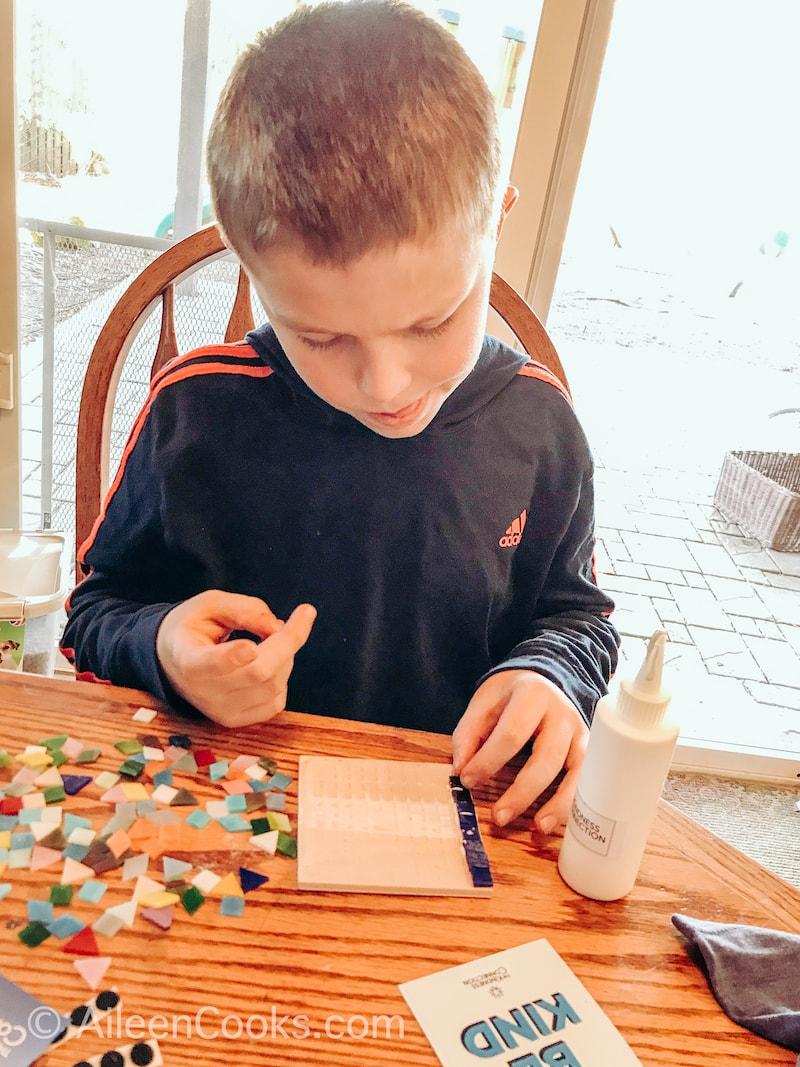 A boy making a mosaic coaster.