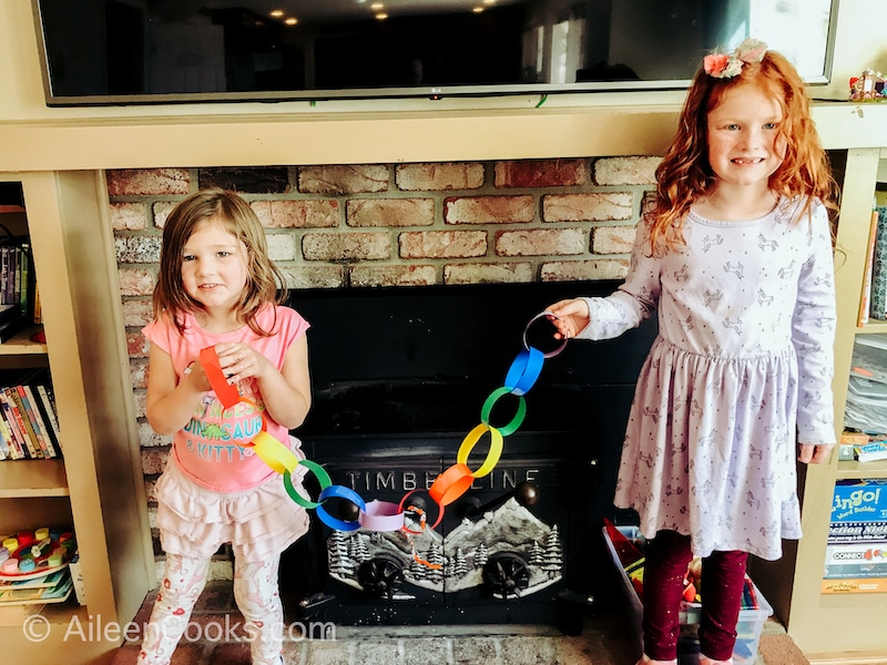 Two little girls holding up a rainbow paper chain.