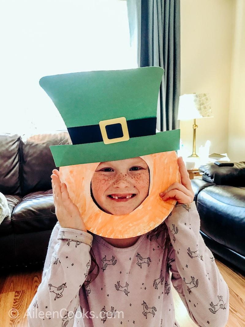 A little girl's face poking through a hand made leprechaun mask craft.
