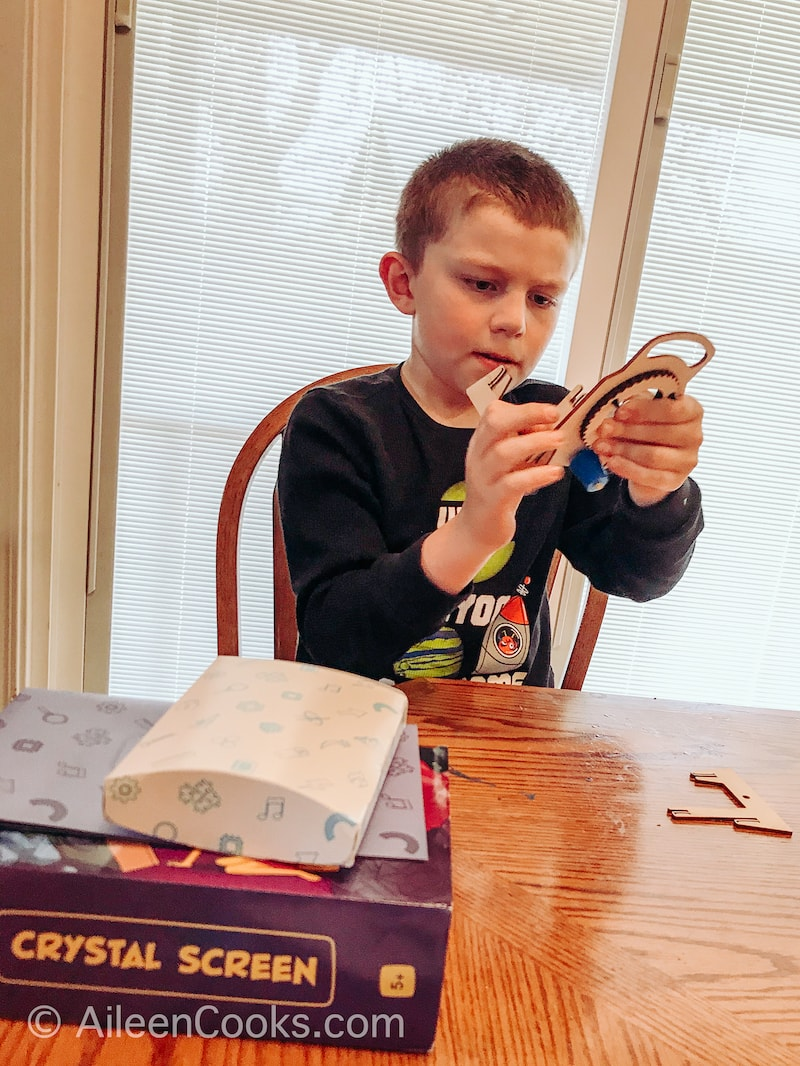 A boy building a crystal screen from Mel Kids box.