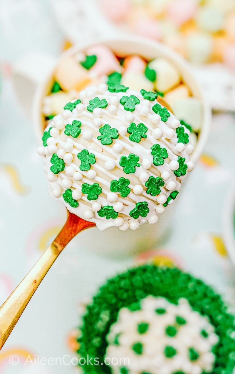 A hot cocoa bomb covered in shamrock sprinkles.
