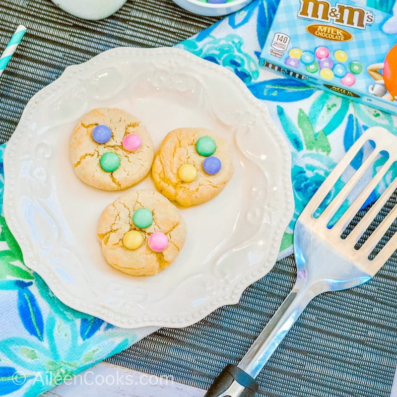 Close up of three M&M cookies on a decorative white plate.