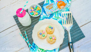 Overhead shot of three Easter cookies on a white plate surrounded by M&Ms, glass bottle of milk, straws, and metal spatula.