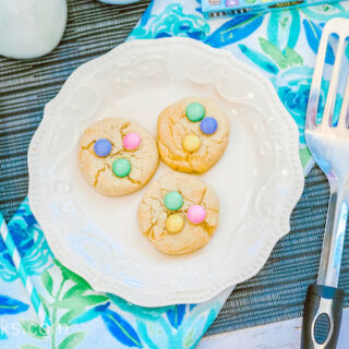 A blue placemat topped with a plate of Easter themed cookies.