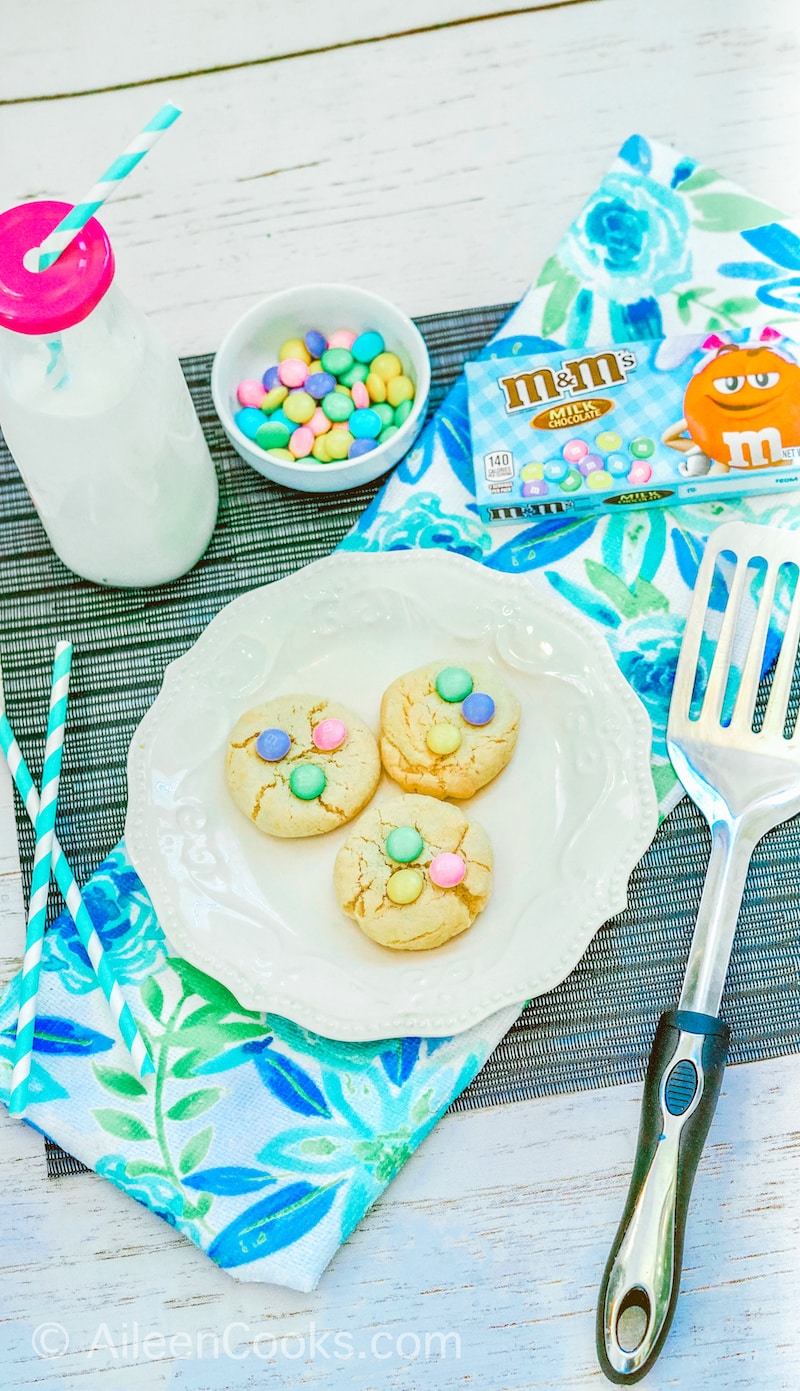 A white plate with three Easter M&M cookies next to a spatula, bottle of milk, and bowl of spring colored M&Ms.