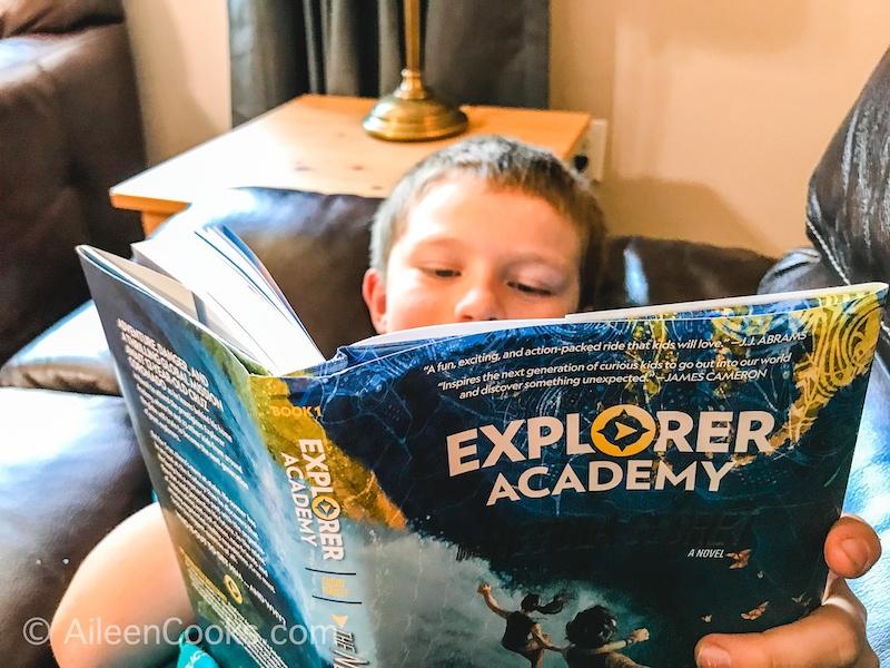 A boy reading Explorer Academy book 1.