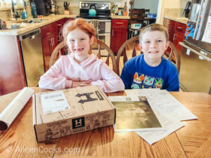 A boy and girl sitting at a table with a History Unboxed subscription box in front of them.