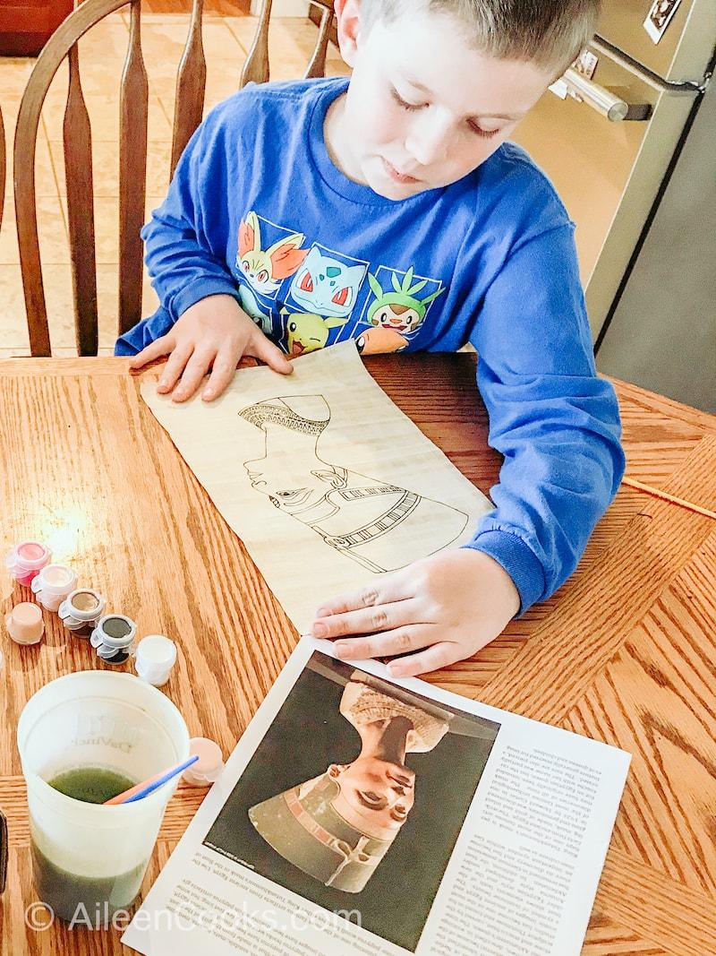 A boy decorating a papyrus scroll.
