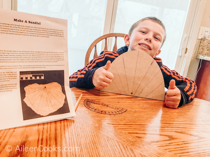 A boy holding up a completed sundial with a thumbs up.