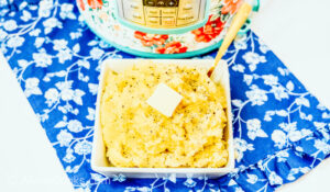 A square bowl of mashed potatoes on top of a blue floral dish cloth.