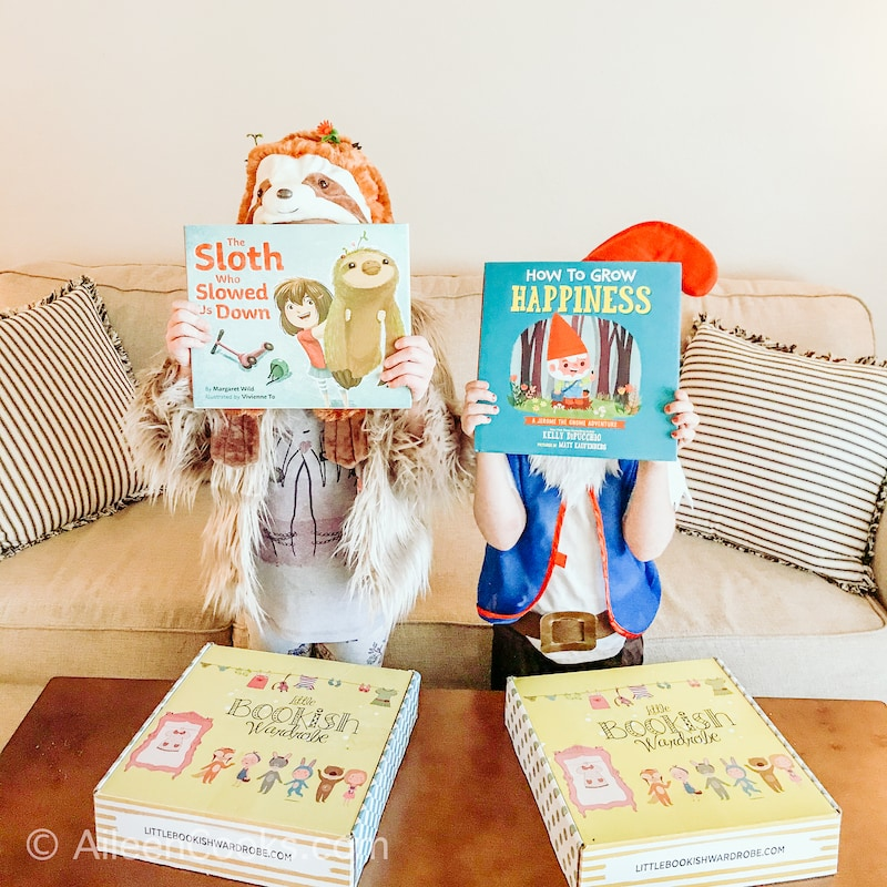 Two little girls holding children's books in front of their faces and dressed as the characters on the cover of the books.