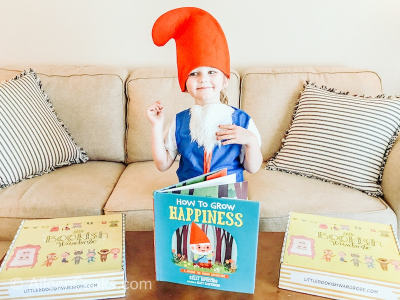 A little girl dressed as an elf with a children's book called How to Grow Happiness.