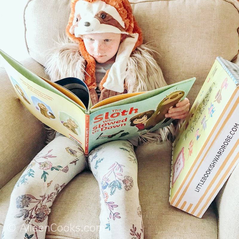 A little girl dressed as a sloth reading a book about a sloth.