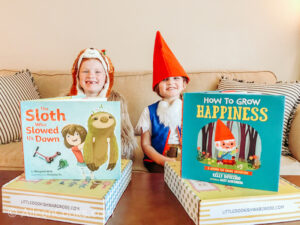 Two kids sitting on a couch in costumes next to two children's books.
