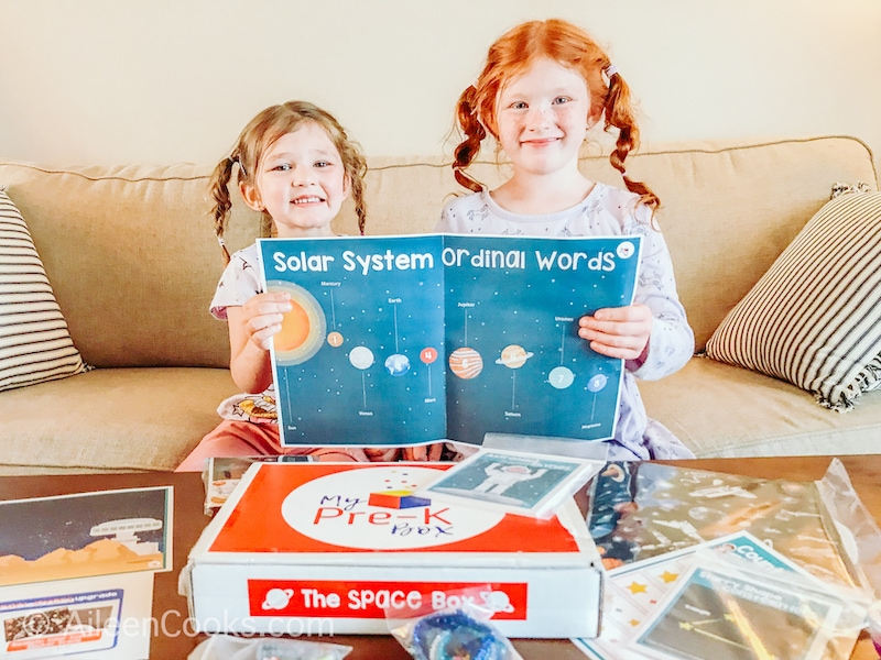 Two girls smiling and holding up a map of the solar system.