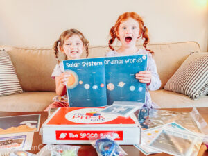 Two girls excited and holding up a map of the solar system.