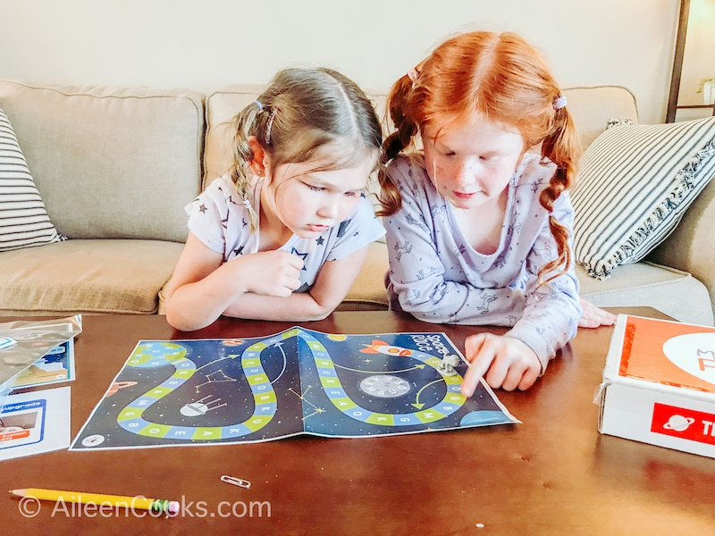 Two little girls leaning over a space-themed board game.