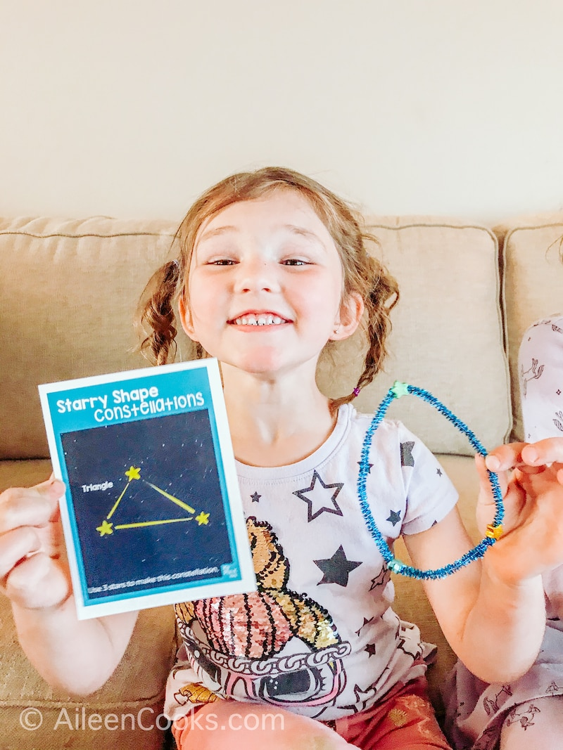 A little girl holding up a picture of a constellation next to her constellation made out of pipe cleaners and star buttons.
