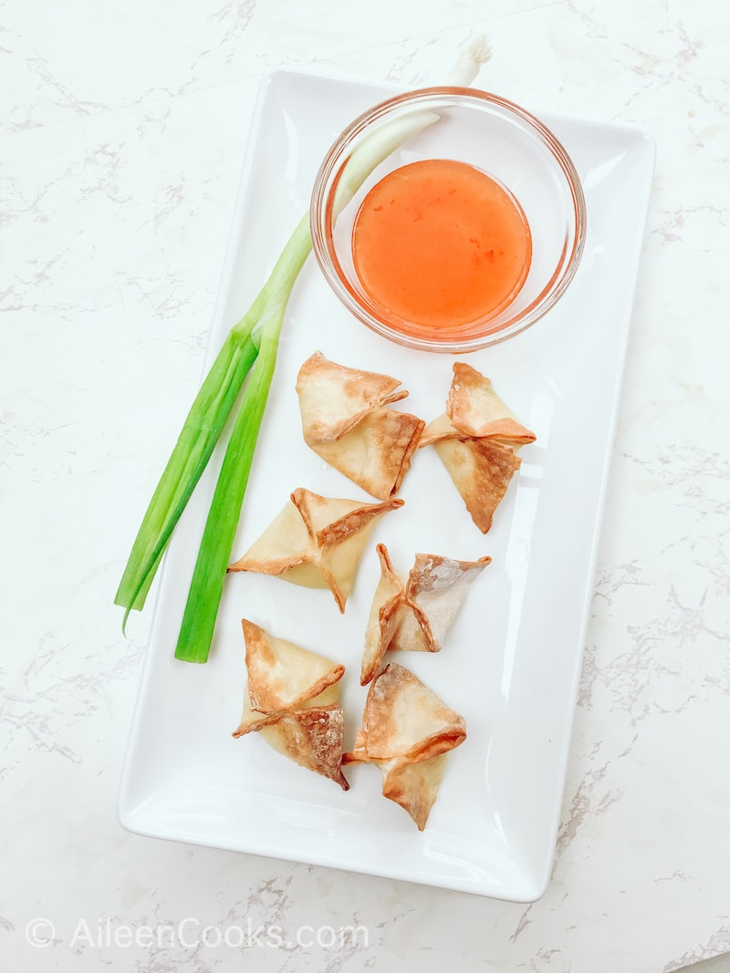 Overhead shot of a white platter with crab Rangoons, small glass bowl of chili sauce, and a green onion.