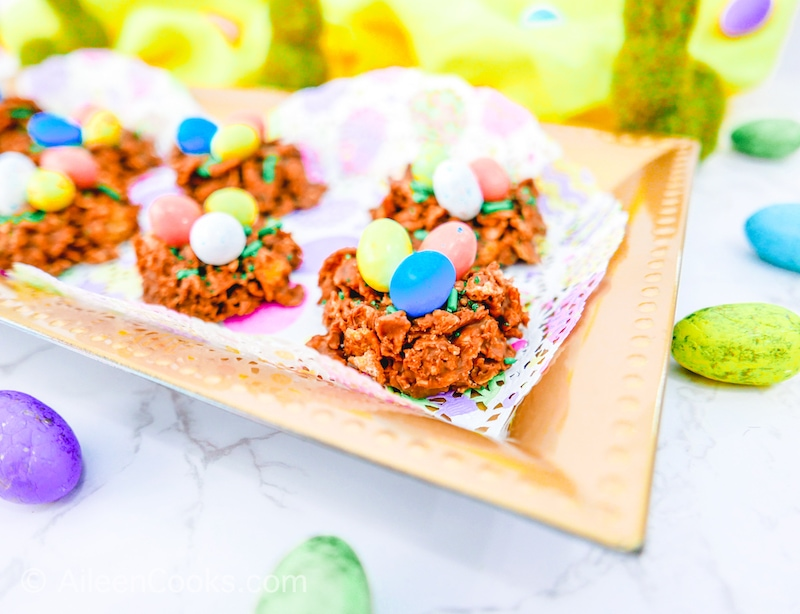 Bird nest cookies on a gold platter with decorative bunnies in the background.