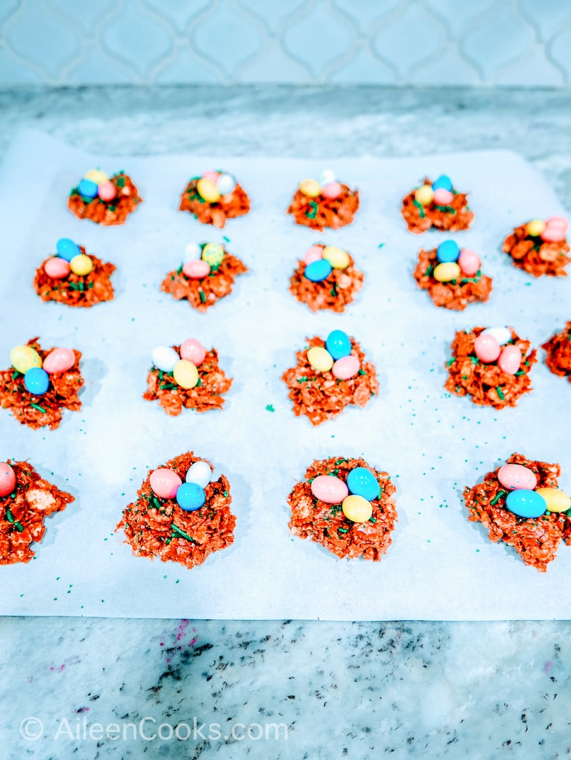 Birds nest cookies arranged on a parchment lined baking sheet.