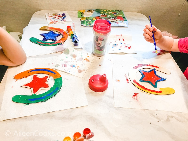 Three kids painting wooden horseshoes.