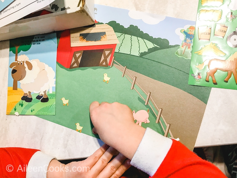 A child's hand putting stickers on a farm scene paper.
