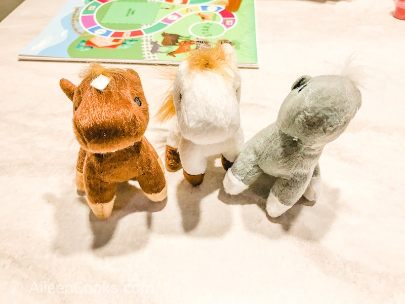 Three small stuffed animals on a white tabletop.