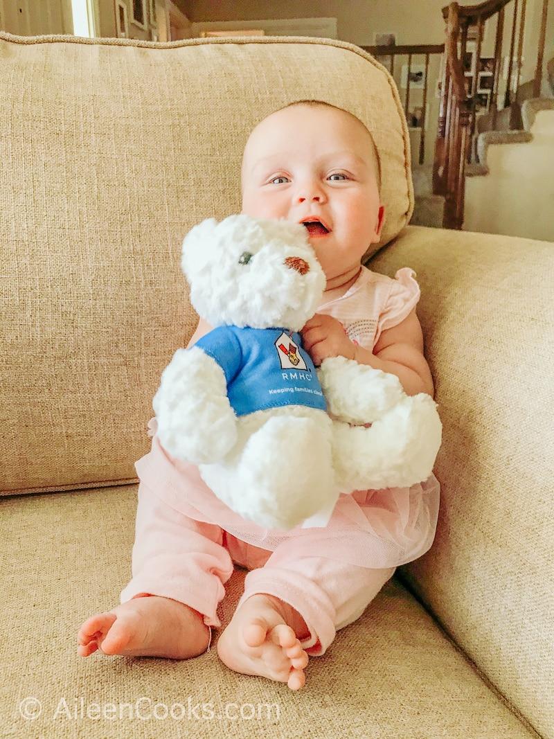 A baby holding a Ronald McDonald House Charities Teddy Bear.