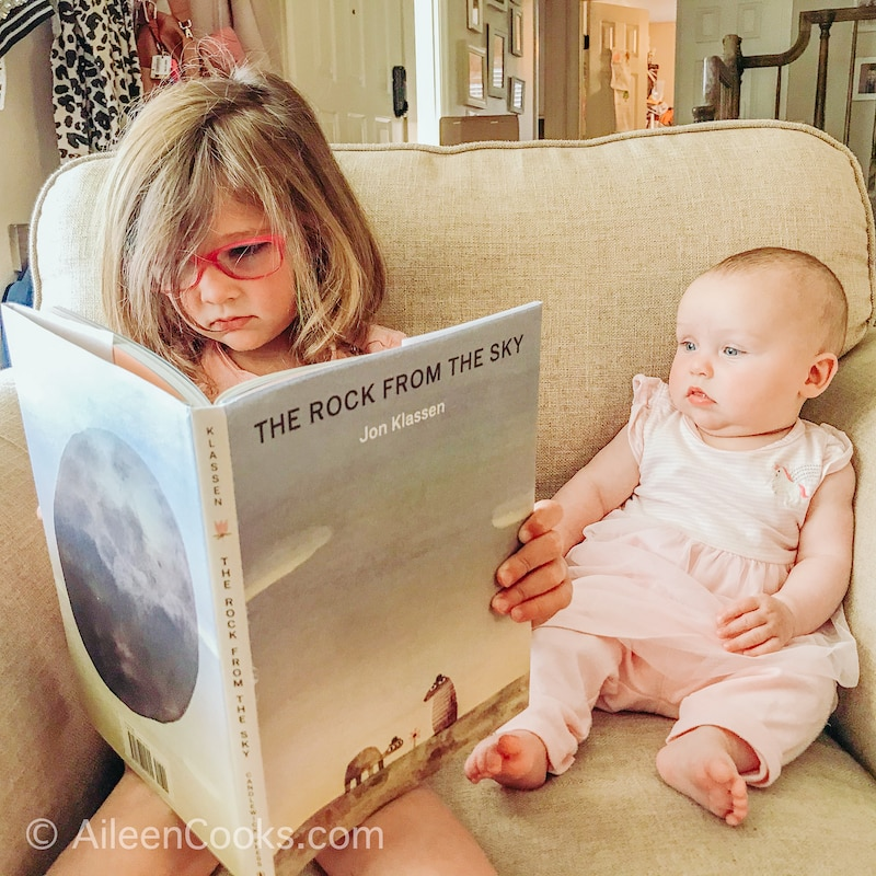 A little girl with pink glasses, reading a book next to her baby sister.