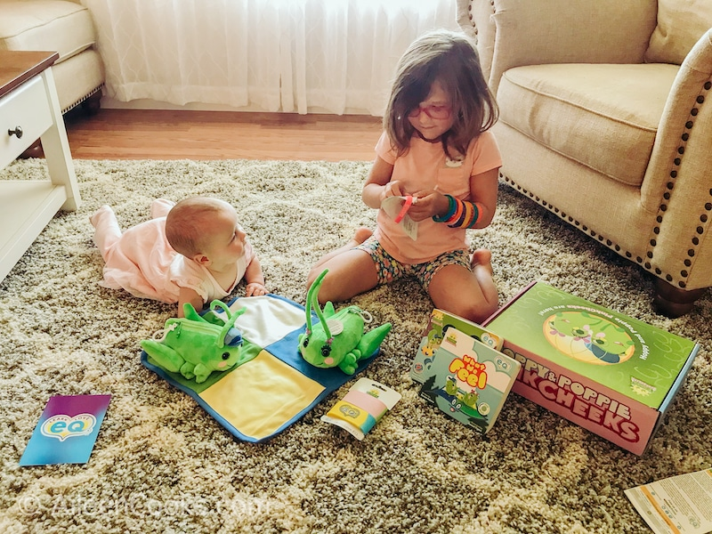 A little girl and baby playing with a box of toys and books.