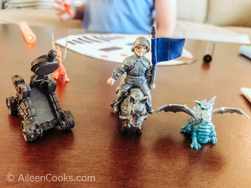 Three small toy figurines on a table, including a knight, dragon, and horse.