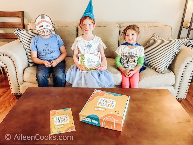 Three kids dressed in costumes to go with the book The Knight and The Dragon.