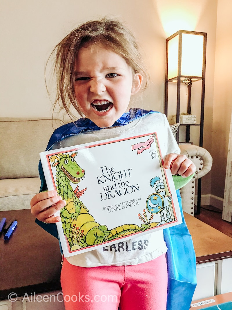 A little girl holding up a book about a dragon and making a scary face.