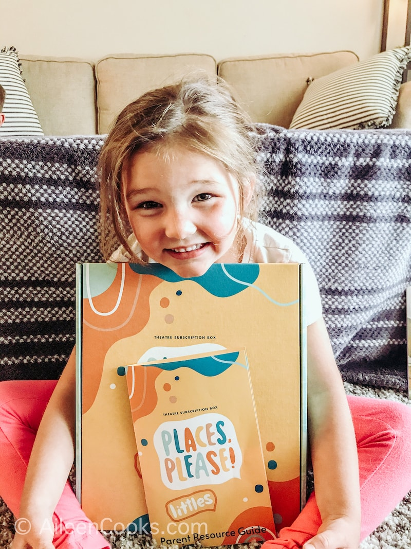 A little girl smiling and holding a Places, Please! Theatre box.