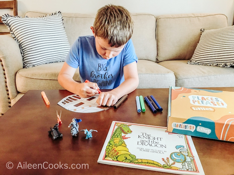 A boy coloring in a knight mask.