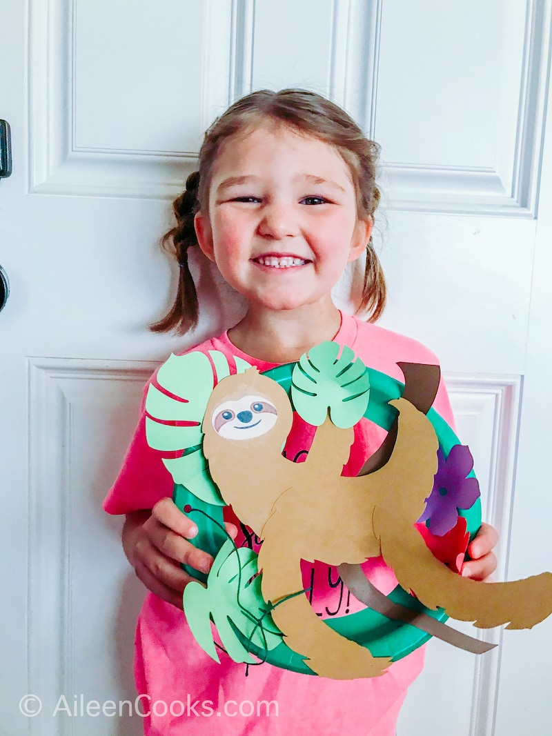 A smiling little girl holding a sloth craft.