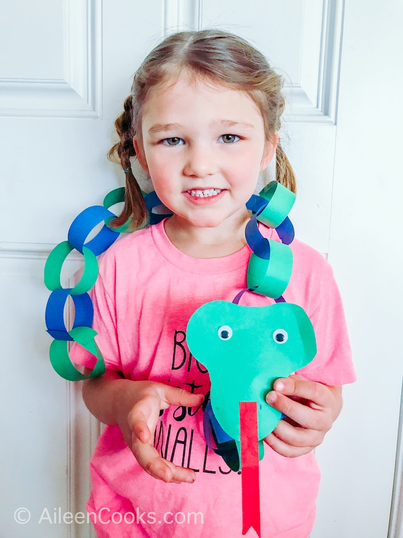 A girl with a boa constrictor craft.