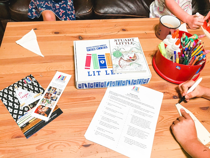 A wood table topped with art supplies, book mark, Lit League Box, discussion questions, and the book Stuart Little.