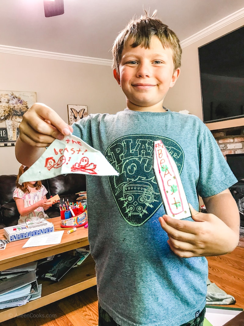 A boy holding the decorated pieces for his model boat.
