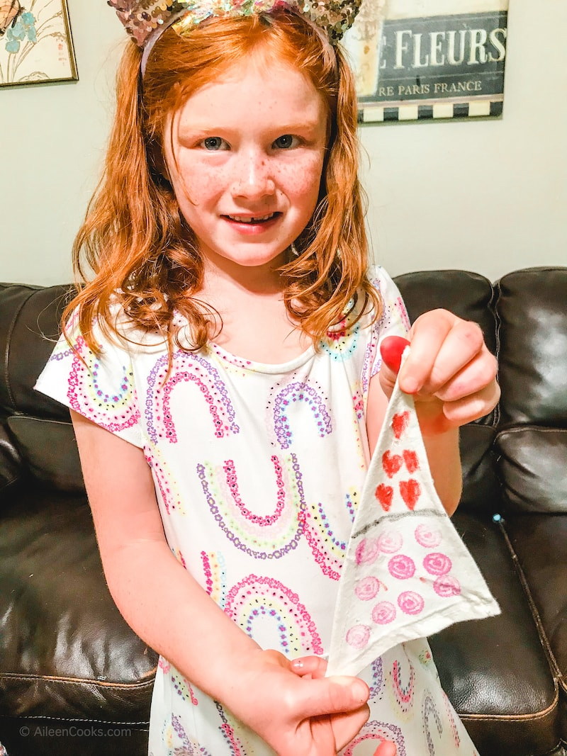 A girl holding her decorated boat sail.