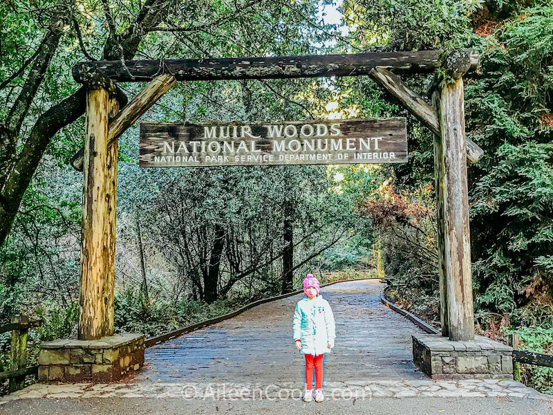 A girl standing under the sign for the Muir Woods National Monument.