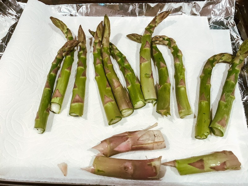 Asparagus drying on a paper towel with ends trimmed off.