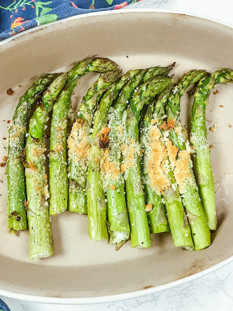 Close up of parmesan roasted asparagus in a white serving dish.