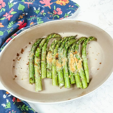 Roasted asparagus topped with parmesan in an oval serving dish.