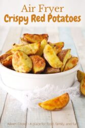 """A white bowl filled with red potato wedges and the words """"Air Fryer Crispy Red Potatoes"""" in brown lettering."""