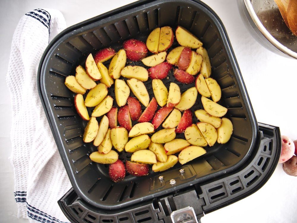 Red potato wedges inside of an air fryer basket.