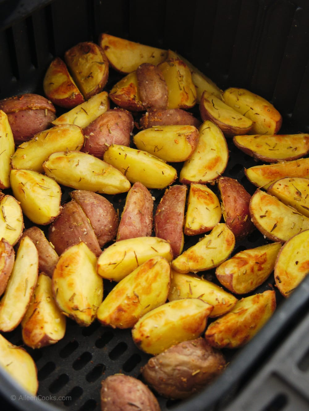 Red potatoes in air fryer after being cooked 10 minutes.