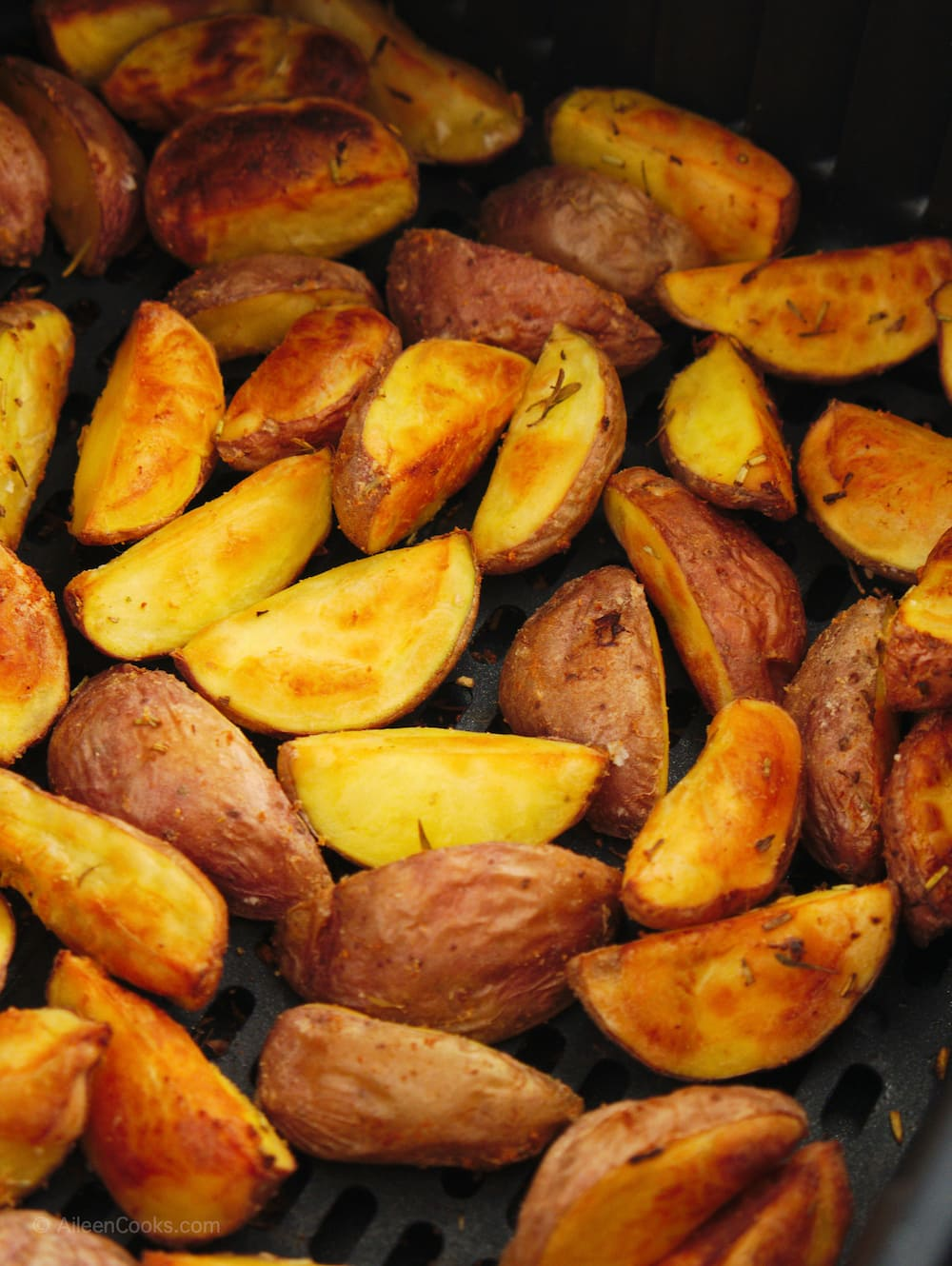 Fully cooked red potatoes in air fryer basket.